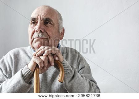 Grey Haired Elderly Man With Mustache Sitting Thinking With His Hands Folded Over The Top Of A Walki