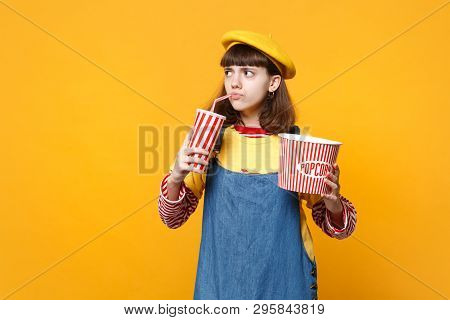 Puzzled Girl Teenager In French Beret, Denim Sundress Hold Plastic Cup Of Cola Or Soda, Bucket Of Po