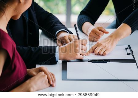 Close-up Of Married Couple Signing Papers Alongside With Other Witness Or Agent - Can Be Divorce, La