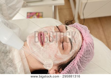Young woman in beauty salon does rejuvenating, toning procedure darsonval on the face. poster