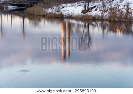 Beautiful Reflection Of Trees And Tall Pipes In The Mirror Smooth Surface Of The River.