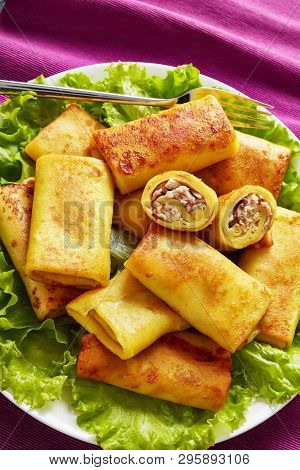 Savory Crepe Rolls With Ground Chicken Meat And Champignon Filling Served On A Bad Of Fresh Lettuce