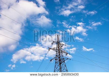 Power Line Transmission Lines Against A Blue Sky With Clouds.