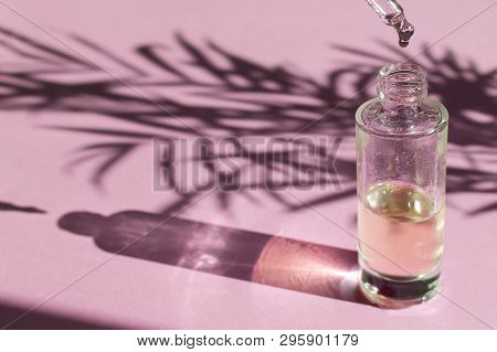 Beauty Skincare Concept - Drop Falls From A Pipette Into A Glass Bottle, Light Pink Background, Copy