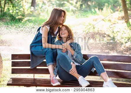 Two Beautiful Young Woman Resting On A Bench