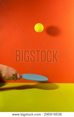 In Hand Racket For Table Tennis With A Ball On Red