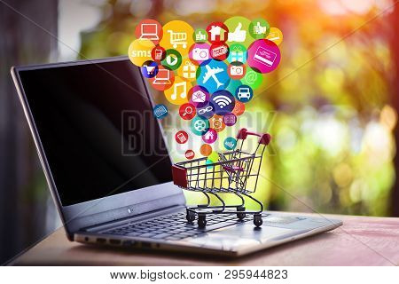 Online Shopping And Online Marketing Concept. Shopping Cart, Laptop On The Desk, Concept Of Buying D