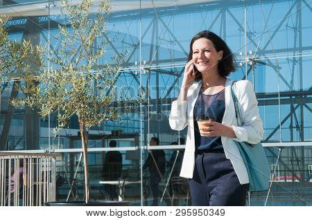 Portrait Of Successful Businesswoman Talking On Mobile Phone. Smiling Mid Adult Woman Walking With C