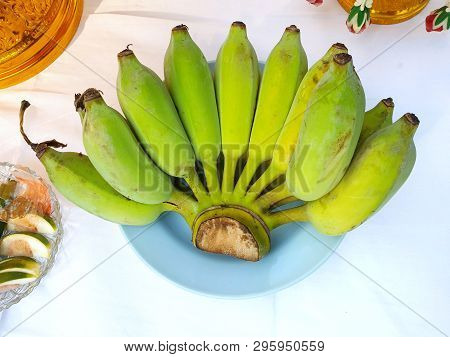 Bunch of banana on blue plate to worship on the table, Top view, Pisang Awak banana poster