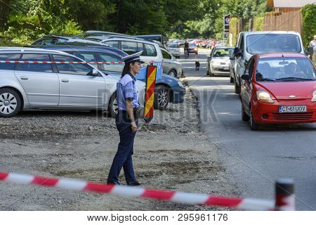 Rasnov, Romania, July 14 , 2018: Woman Police Agent Guarding Parking Place In Front Of The Rasnov Fo