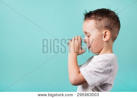 a child drinks water on a turquoise background