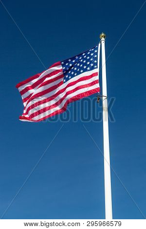 The Flag Of The United States Of America Waving In The Wind Witha  Clear Blue Sky.