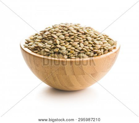 Uncooked dried lentil in wooden bowl isolated on white background.