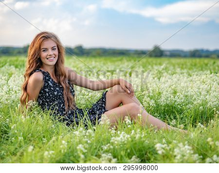 Model posing in a field of white lavendar flowers. Young cheerful woman sitting outdoors in a field of white flowers.