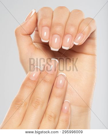 Beautiful female hands. Woman hands with beautiful french manicure, nails.  Hand care. Woman cares for the nails on hands. Beauty treatment with skin of hand.   Woman's hands close-up view.