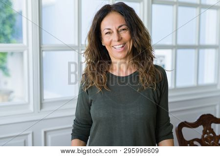 Beautiful middle age woman at home smiling cheerful