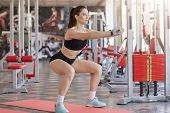 Sporty girl with dark hair and ponytail wearing blue snickers, dark short and black short top doing squatting at gym, has concentrated expression. Sport, healthy lifestyle, motivation, fitness concept poster
