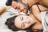 Happy romantic couple having sex - Young lovers during foreplay having tender and intimate moments in the bed - People, sexual, love and relationship concept poster