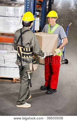Two happy foremen carrying cardboard box at warehouse