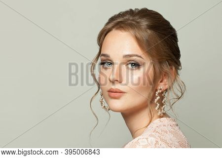 Pretty Woman Face. Nice Woman With Ginger Hair And Pastel Color Makeup On White Background.