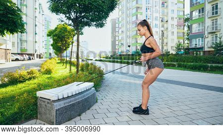 Side View Of Young Pretty Woman Training Upper Body, Practicing Exercises Using Fitness Elastic Rope