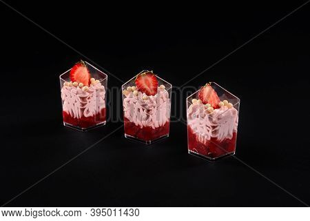 Three Small Glasses Filled With Whipped Pink Cream And Red Jam Decorated With Fresh Strawberries And