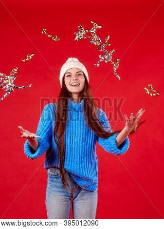Beautiful Girl In A Warm Sweater Throws Shiny Tinsel On A Red Background.
