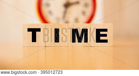 The Word Time Written On Cubes With A Red Clock In The Background. A Reminder That Time Is Running O