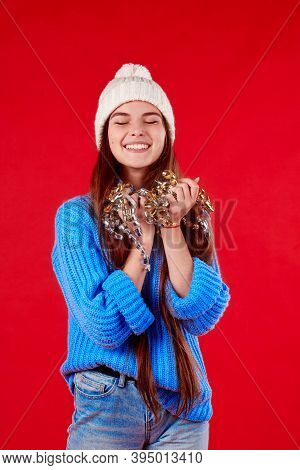 Beautiful Girl In A Warm Sweater And White Hat Holding Shiny Tinsel On A Red Background.