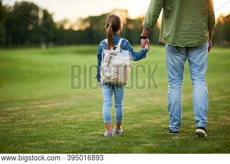 Rear View Of Little Girl With Backpack Holding Fathers Hand, While Spending Time With Her Daddy In T