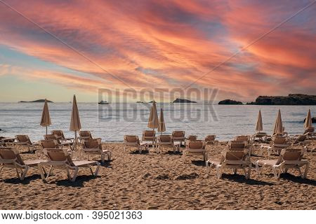 Folded Parasols And Lot Of Deckchairs On The Sandy Empty Beach Of Ibiza During Sunset Bright Cloudy