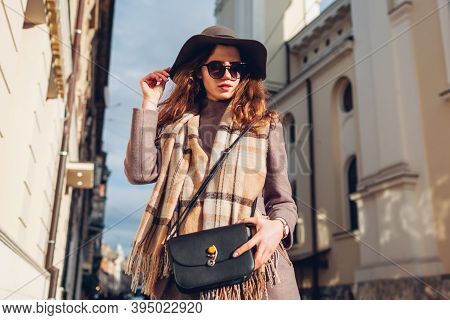 Street Female Fashion. Portrait Of Stylish Young Woman Wearing Hat Glasses Holding Purse Outdoors. A