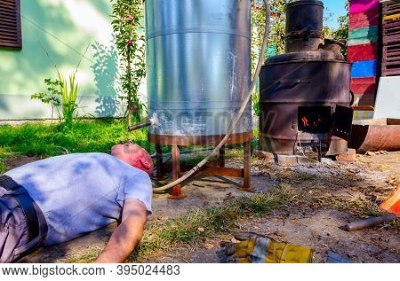 Man Lies Below Distillation Apparatus And Drinking Fresh Moonshine Schnapps, Alcoholic Beverages Suc
