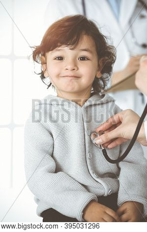 Woman-doctor Examining A Child Patient By Stethoscope In Sunny Clinik. Cute Arab Toddler At Physicia
