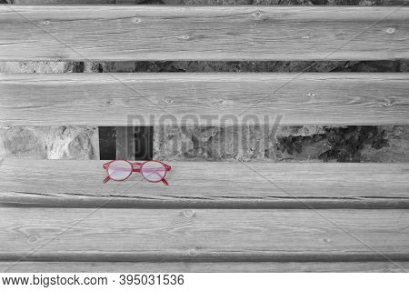 Spectacles With Red Rim Lying On A Bench. Black And White Background, But Colored Spectacles