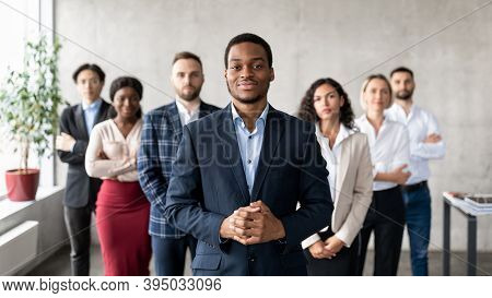 Leadership. Successful African Businessman Standing With His Business Team In Modern Office, Smiling