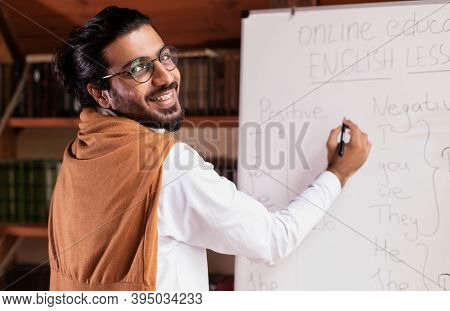 Distance Education. Happy Indian Teacher Man Teaching Remote Students Online Pointing To Blackboard