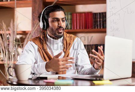 Indian Teacher Teaching Online Having Webinar Sitting At Laptop Making Video Call Communicating With