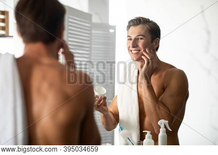 Male Facial Skincare Concept. Smiling Handsome Man Applying Cream On Smooth Face Caring For Skin Aft