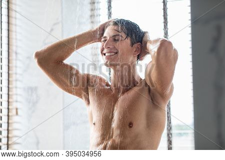 Selfcare And Wellness Concept. Portrait Of Smiling Handsome Young Man Taking A Shower Standing Under
