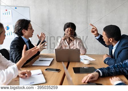 Discontented Coworkers Shouting At Unhappy Victimized Businesswoman Sitting At Table In Modern Offic
