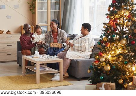 Portrait Of Two Generation African-american Family Decorating Home For Christmas Together While Enjo