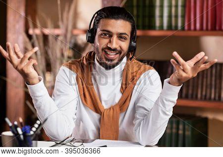 Smiling Arab Teacher Guy Talking To Camera Teaching Online Wearing Headphones Having Distance Class