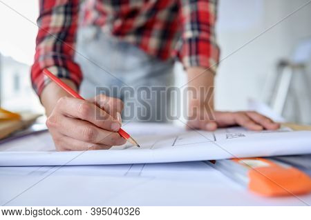 Engineer Working Alone At Construction Property Site. Architecture With Project On Blueprint For Mas