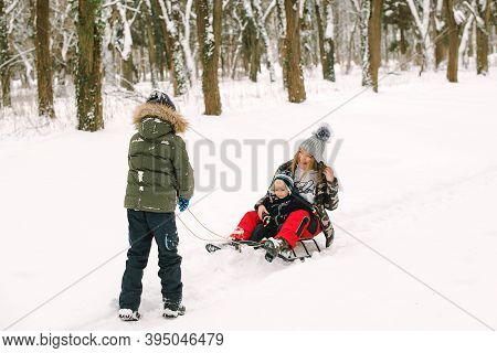 Mother And Children Enjoying Sleigh Ride. Happy Family With Sled In Winter Having Fun Together. Fami