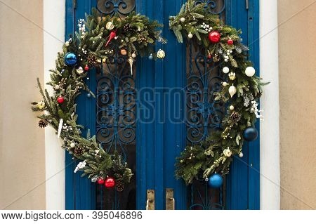 Large Christmas Wreath From A Christmas Tree On A Blue Old Door With Openwork Forging. Festive Decor