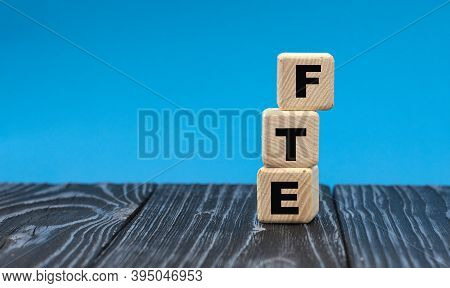 Abbreviation Fte (full Time Equivalent) On Wooden Cubes On A Blue Background. Business Concept