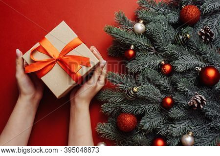 Craft Gift With A Red Ribbon In The Hands Of A Young Girl With A Nude Manicure Next To The Branches