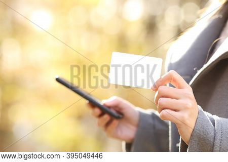 Close Up Profile Of Woman Buying Online With Smart Phone Showing Blank Credit Card In Fall In A Park
