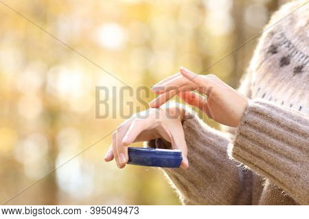 Close Up Of Woman Hand With Dry Skin Applying Moisturizer Cream In Autumn In A Park